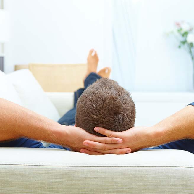 Mann liegt auf dem Sofa